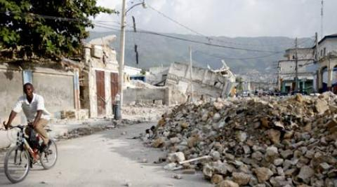A man riding his bike past the rubble left by the Haiti earthquake.