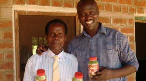 Innocent Ogaba and Mr Laston holding moringa jars