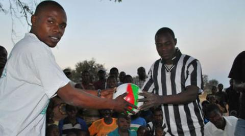 Two men holding a football in Malawi