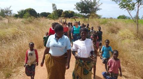 Women walking through a field in Malawi
