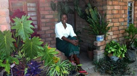 Portrait of Nifa Chumachiyenda, a farmer in Malawi, outside her house