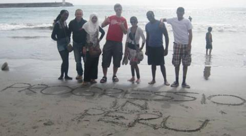 "Empower volunteers on the beach in Lima, writing in the sand ""Progressio Peru"""