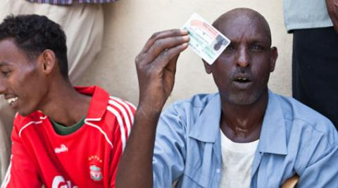 A man holds up his voter ID card in Somaliland