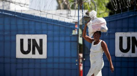 A woman walks by a UN base carrying a bag of rice in Port-Au-Prince, Haiti, 2010