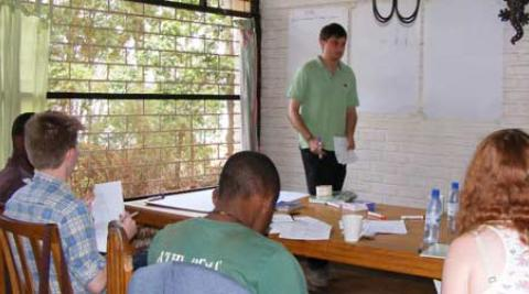 Sam, a UK volunteer, helps the rest of the UK group to learn Chichewa