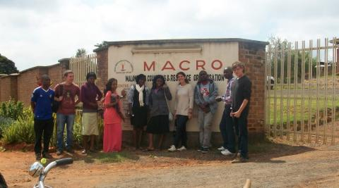 Volunteers standing outside the Malawi AIDS Counselling & Resource Organisation