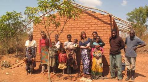 Rose Kumwenda (third right) and family in front of her newly built house constru