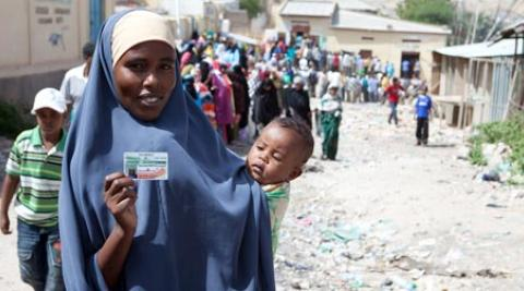 Somaliland woman holds ID card in queue to vote