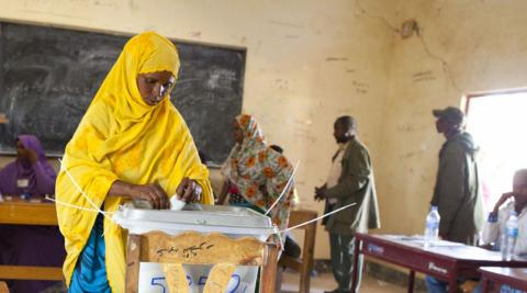 Woman places vote in ballot box, Somaliland