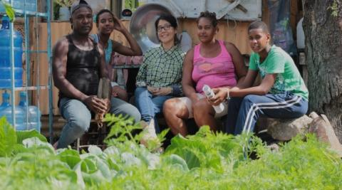 The Fleming family and Progressio Development Worker, Nadie, sitting in their vegetable garden