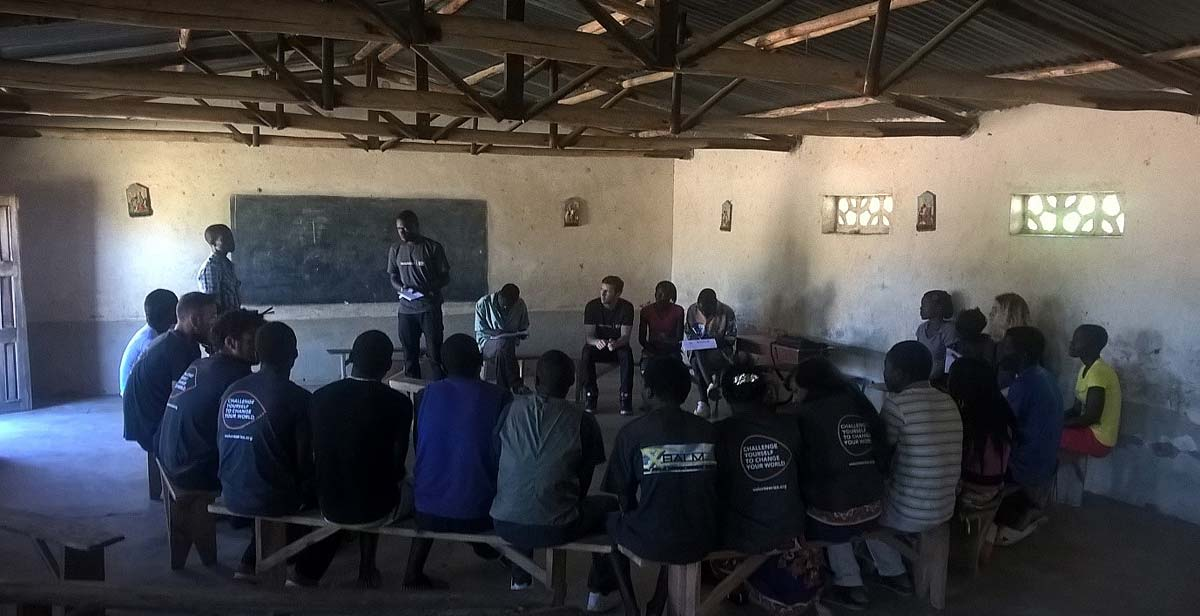 Team member Patrick addressing Chasato Youth Club leaders and members and translating English and Chitumbuka