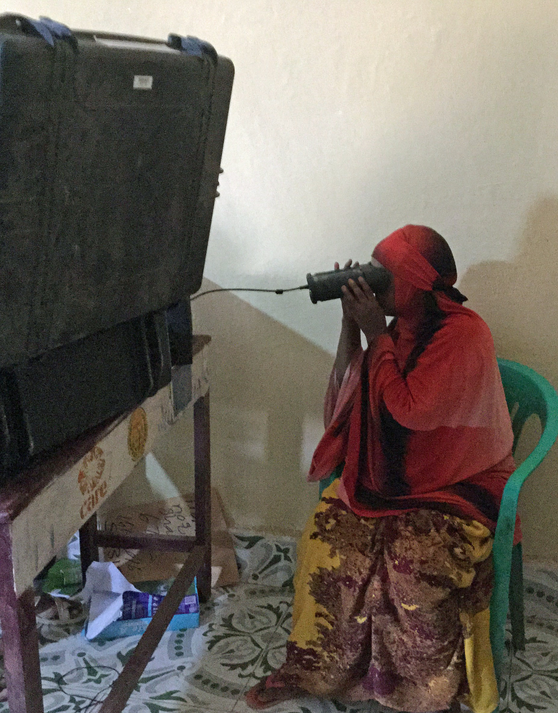 A female voter uses new iris-recognition technology
